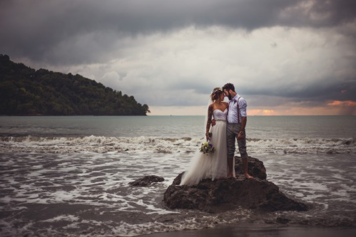 newlyweds on beach, bride and groom on beach, bride and groom on a rock, beach wedding, costa rica weddings, vintage beach wedding, tulemar, weddings costa rica