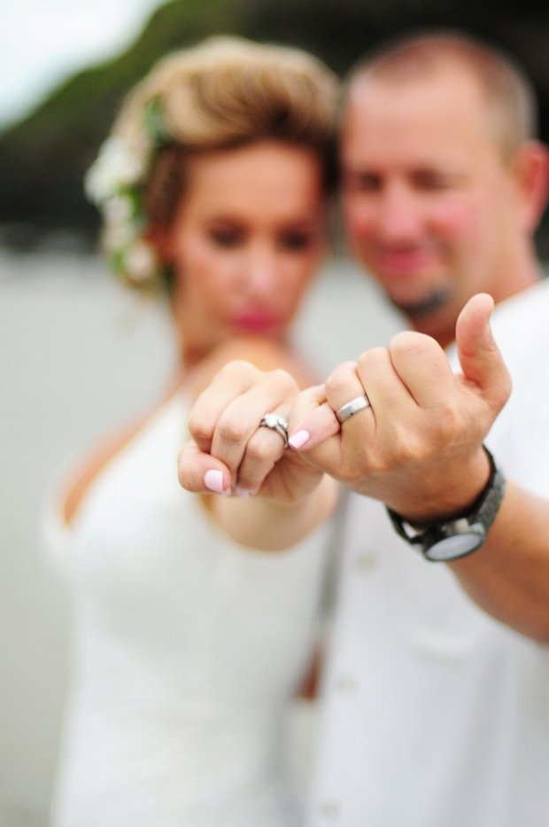 couple showing off wedding rings